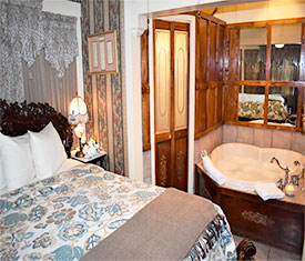 Sunshine room queen bed and heart shaped whirlpool tub at The Gables Inn