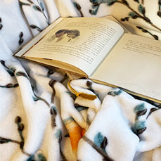 Book laying on throw blanket at The Gables Inn